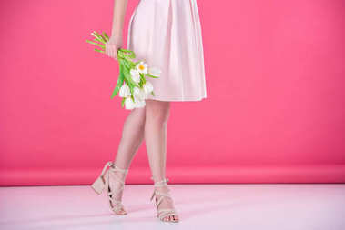 cropped image of girl in pink dress with bouquet of tulips on pink