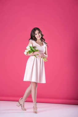 attractive girl in pink dress with bouquet of tulips looking away on pink