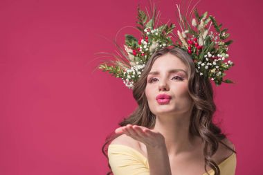 beautiful girl with flowers and herbs wreath on head sending air kiss isolated on burgundy