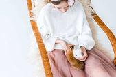 Fotografia vista di alto angolo della ragazza con simpatici coniglietti pelose che si siede nella sedia a dondolo
