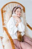 Fotografia bella ragazza adolescente felice che abbraccia conigli mentre seduto nella sedia a dondolo su bianco