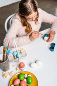 high angle view of cute focused child painting easter egg at table