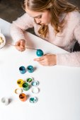 beautiful focused teenage girl painting easter egg at table
