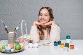 adorable happy girl smiling at camera while sitting at table with paints, basket and easter eggs