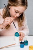 adorable focused girl painting easter egg