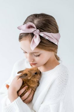 close-up view of beautiful teenage girl holding adorable furry rabbit isolated on white