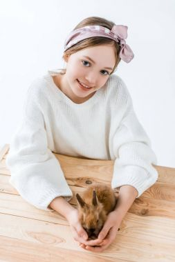 beautiful little girl smiling at camera while holding cute furry rabbit