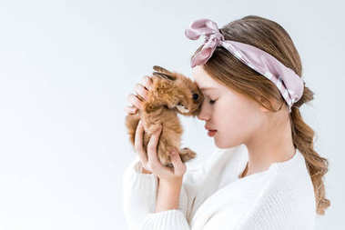 side view of beautiful little girl holding furry rabbit isolated on white