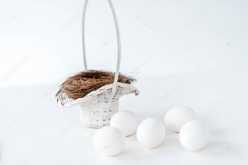 close-up view of white chicken eggs and nest in wicker basket on white