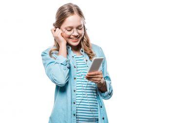 adorable happy girl in earphones using smartphone isolated on white