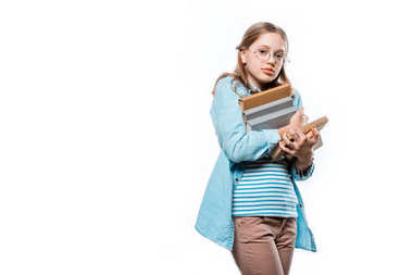 cute teenage girl in eyeglasses holding stack of books and looking at camera isolated on white