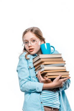 girl in eyeglasses holding stack of books with cup on top and looking at camera isolated on white