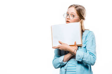 teenage girl in eyeglasses holding blank book and looking at camera isolated on white
