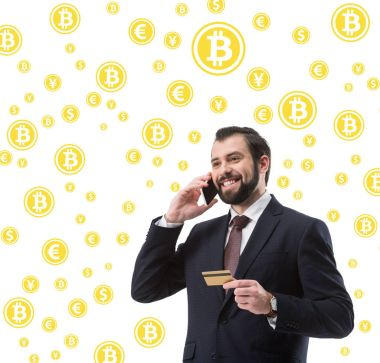 businessman with credit card talking on smartphone, bitcoin and money symbols isolated on white