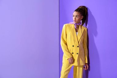 african american girl posing in yellow suit, on trendy ultra violet background