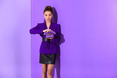 african american girl posing in purple jacket and holding vintage rotary telephone at ultra violet wall