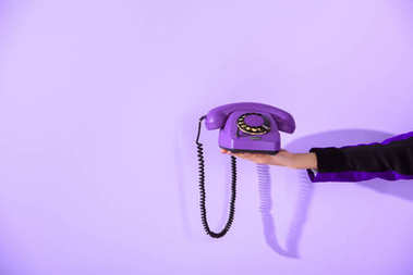 cropped view of girl holding vintage rotary phone at ultra violet wall