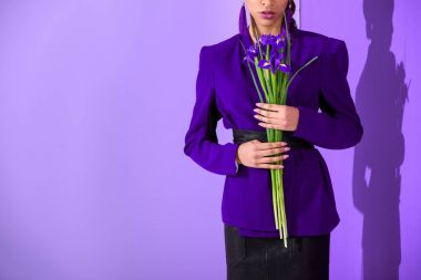 cropped view of mulatto girl posing in purple jacket with irises at ultra violet wall