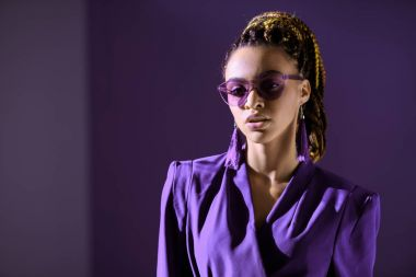 fashionable african american girl posing in trendy ultra violet jacket and sunglasses