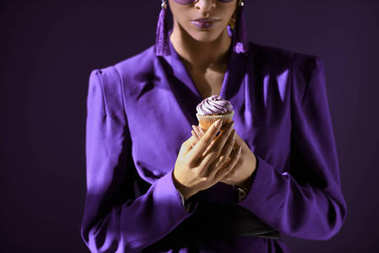 Cropped view of african american girl in ultra violet jacket with cupcake, isolated on dark purple