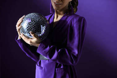 Cropped view of girl posing in trendy purple jacket with disco ball, isolated on purple