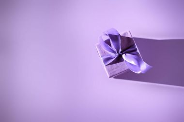 top view of gift box with purple bow, ultra violet trend