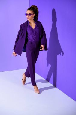 beautiful fashionable african american girl posing in purple suit, ultra violet trend