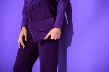 cropped view of girl in purple suit holding purple diary, ultra violet trend of 2018 year
