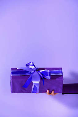 cropped view on female hand holding purple present, isolated on ultra violet