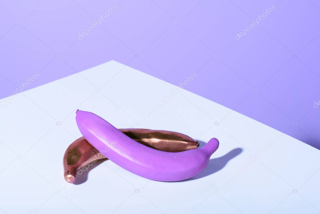 plastic purple and golden bananas on violet surface