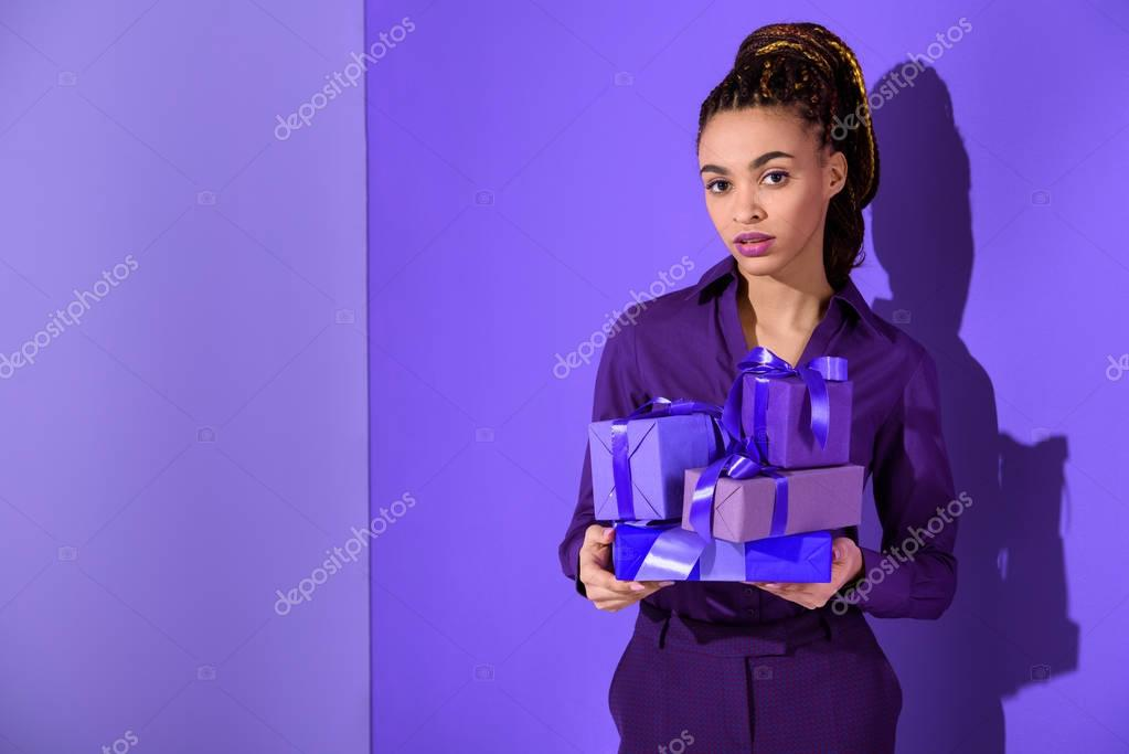 beautiful mulatto girl holding purple presents, ultra violet trend