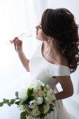 krásná mladá nevěsta s svatební kytice pití šampaňského