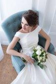 atraktivní nevěsta s svatební kytice sedí v křesle