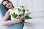 Selektivní fokus nevěsty s svatební kytice sedí v křesle