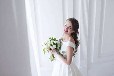 happy young bride posing in elegant white dress with wedding bouquet