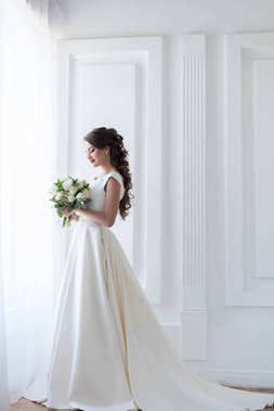 bride posing in elegant white dress with wedding bouquet