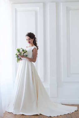 smiling bride posing in elegant dress with wedding bouquet