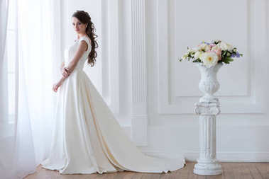 Beautiful bride posing in elegant wedding dress near bouquet of flowers in vase stock vector