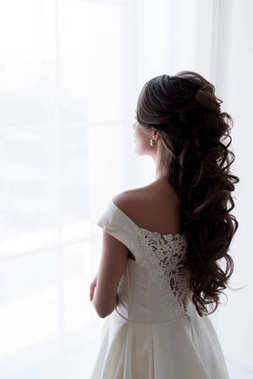 back view of bride in wedding dress looking at window