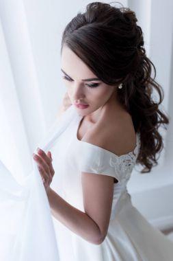 attractive brunette woman posing in wedding dress