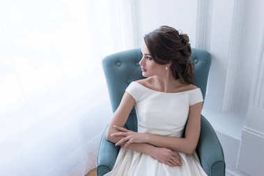 brunette woman in wedding dress sitting in armchair and looking at window