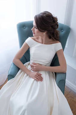 attractive young bride in wedding dress sitting in armchair