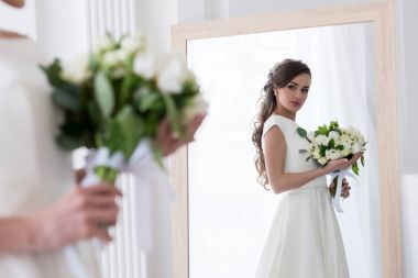 beautiful bride in dress with wedding bouquet looking at her reflection in mirror