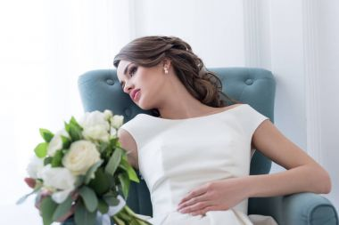 young bride with wedding bouquet sitting in armchair