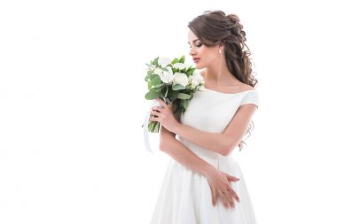 elegant bride posing in traditional white dress with wedding bouquet, isolated on white