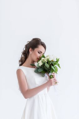 attractive bride with closed eyes sniffing wedding bouquet, isolated on white
