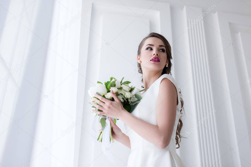 young bride posing in traditional white dress with wedding bouquet