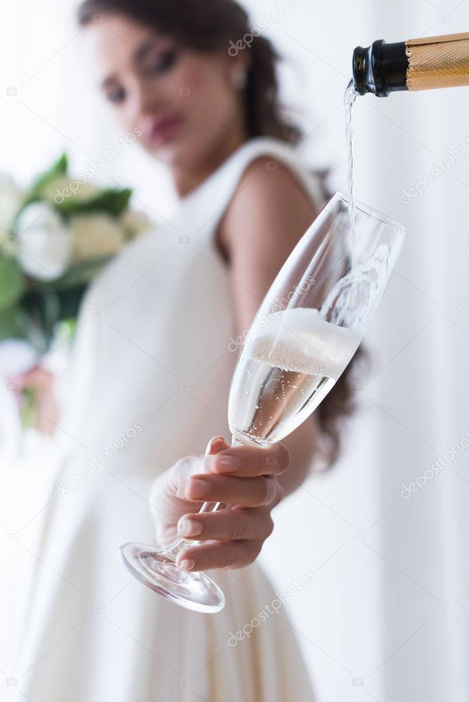 selective focus of bride holding glass of champagne