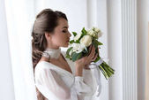 Fotografie attractive bride in wedding dress and veil sniffing white bouquet