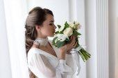 Fotografie atraktivní nevěsta svatební šaty a závoj čichání bílá kytice